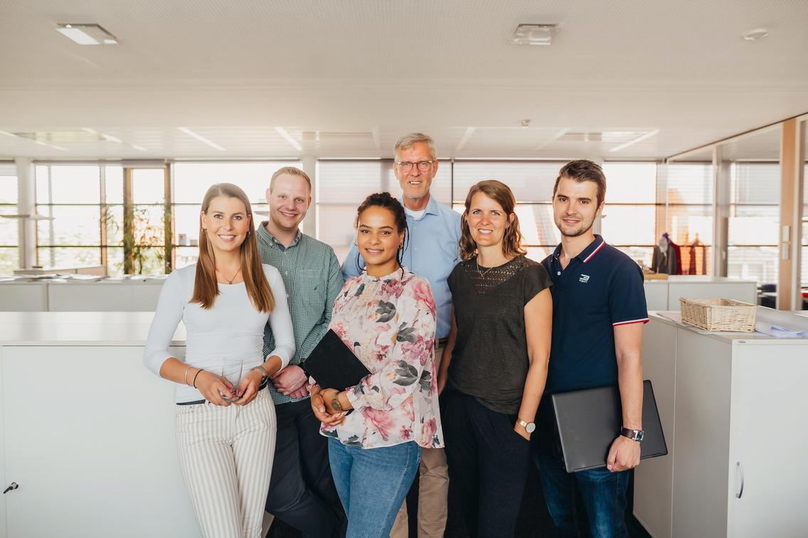 Gruppe von Berufserfahrenen und -einsteigenden steht im Büro