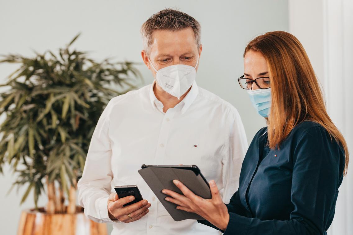 Zwei Kollegen schauen auf ein Tablet