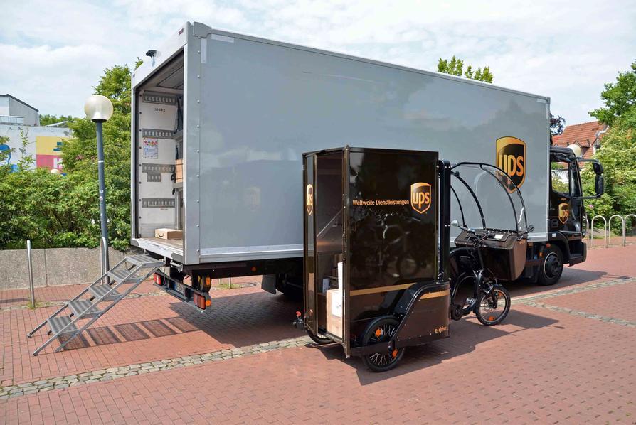 """Am temporären City-Hub an der Vitihof-Garage werden die Pakete vom UPS-Transporter auf das E-Cargo-Bike """"MovR"""" umgeschlagen."""