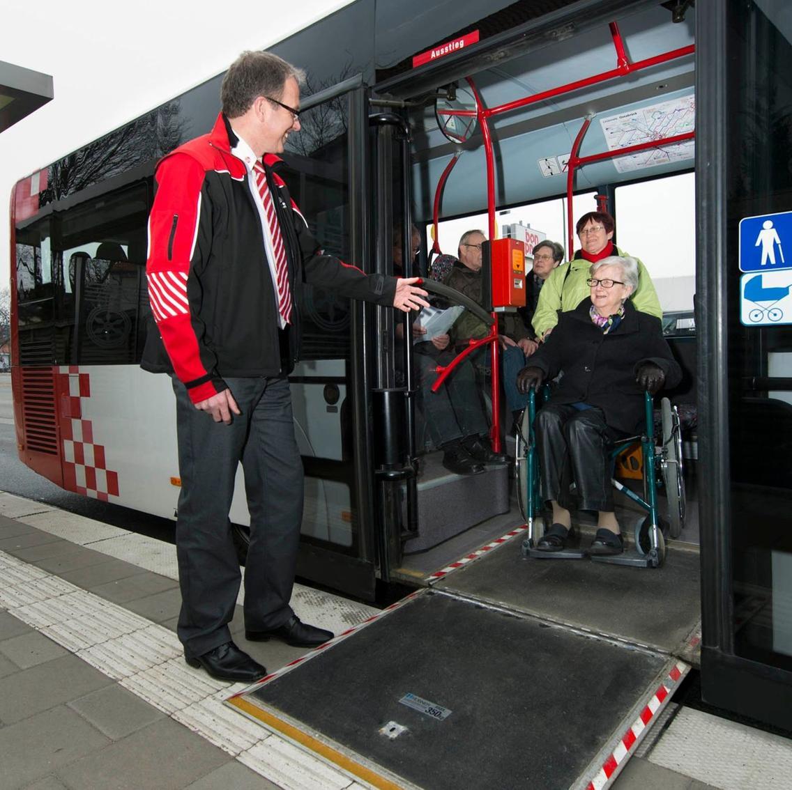 Busfahrer klappt Rollstuhlrampe für Frau im Rollstuhl aus