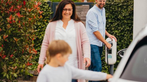 Familie lädt Ihr E-Auto an einer Ladebox Zuhause