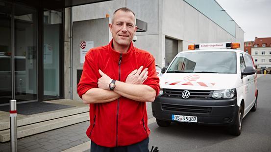 Ein Mitarbeiter des Entstörungsdienstes steht vor dem Dienstwagen
