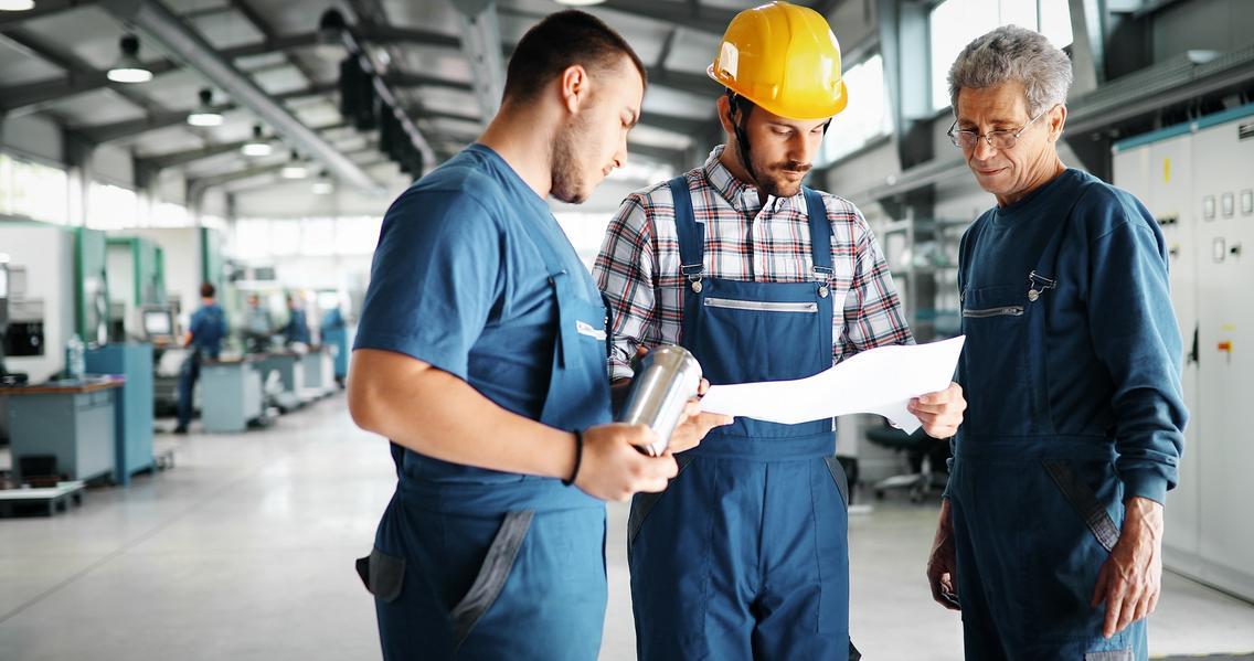 Männer unterhalten sich in Werkhalle einer Firma