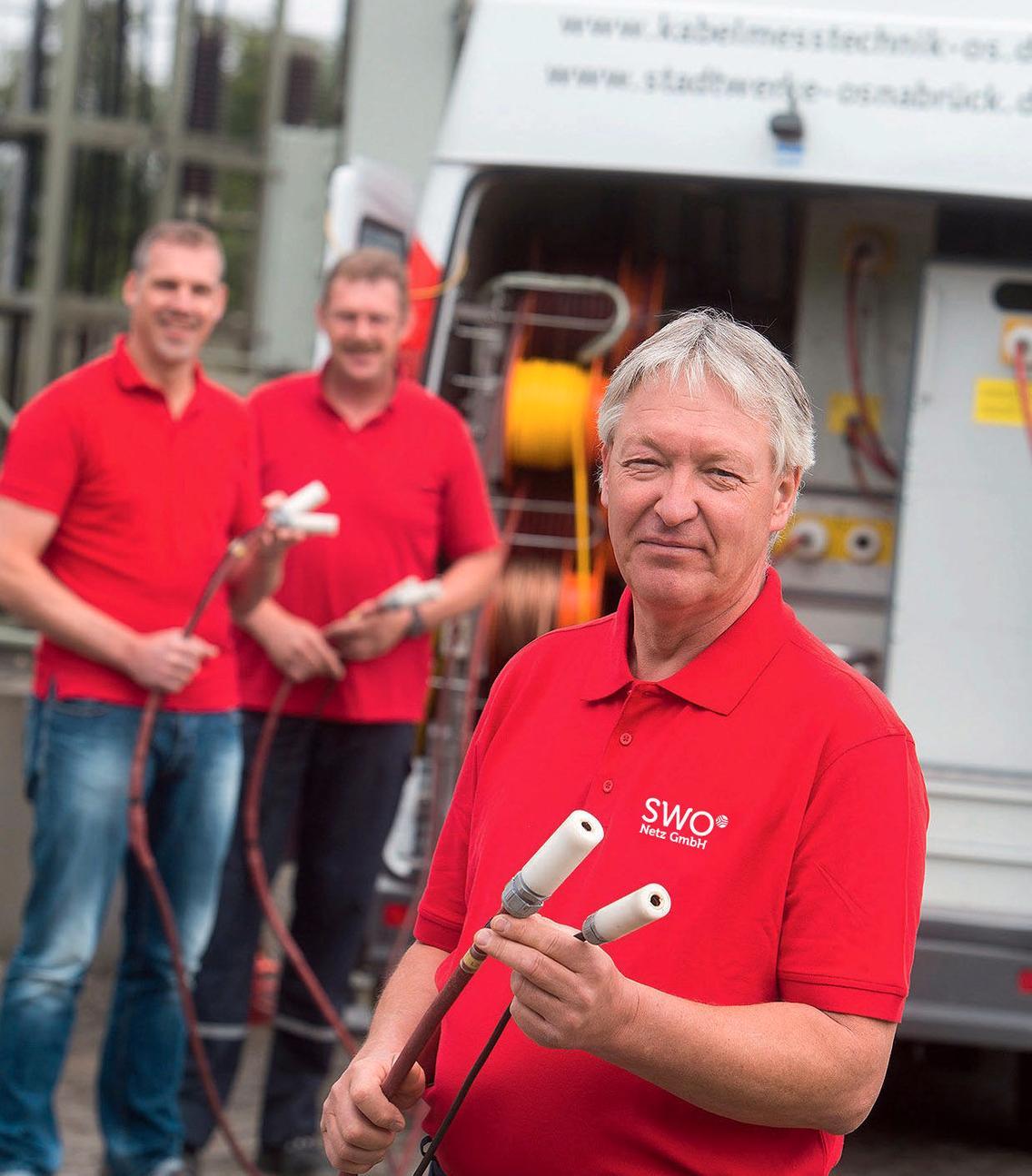 Mitarbeiter der SWO Netz GmbH stehen vor dem Messtechnikwagen
