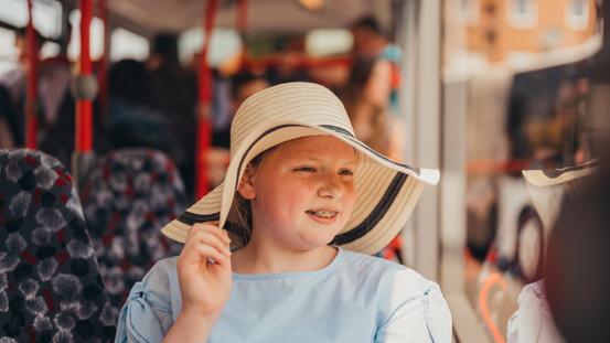 Schülerin mit Hut fährt mit Sommerferienticket