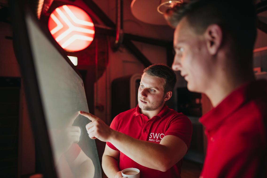 Studierende besprechen sich am Touch-Monitor