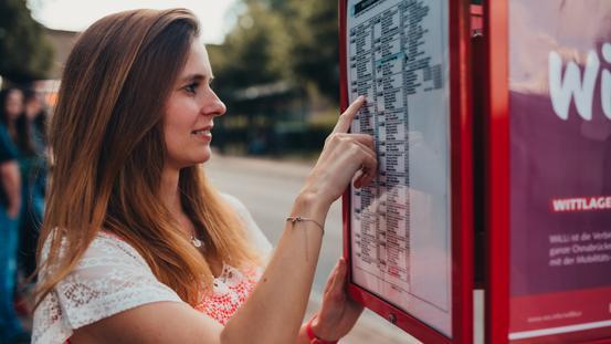 Frau an Haltestelle der VOS sucht eine Bus-Verbindung