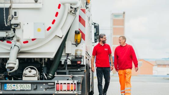 Mitarbeiter laufen neben einem Klärwerks-Fahrzeug
