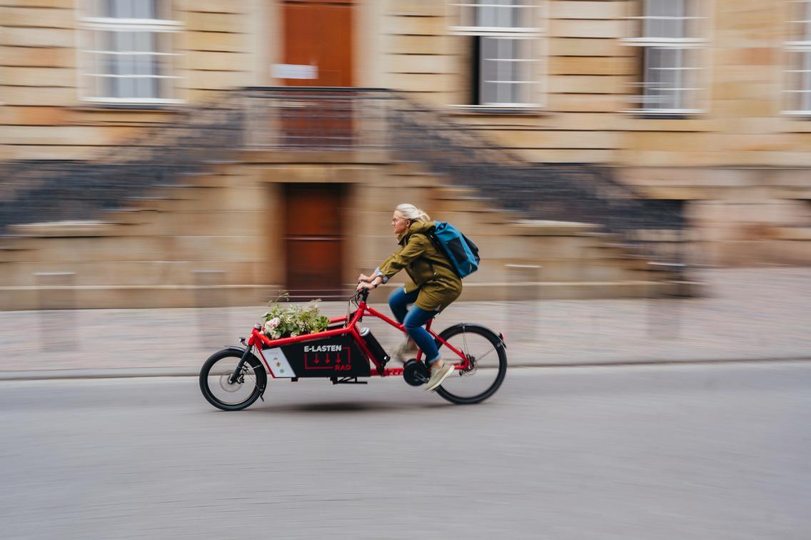 Frau fährt mit dem E-Lastenrad durch die Stadt