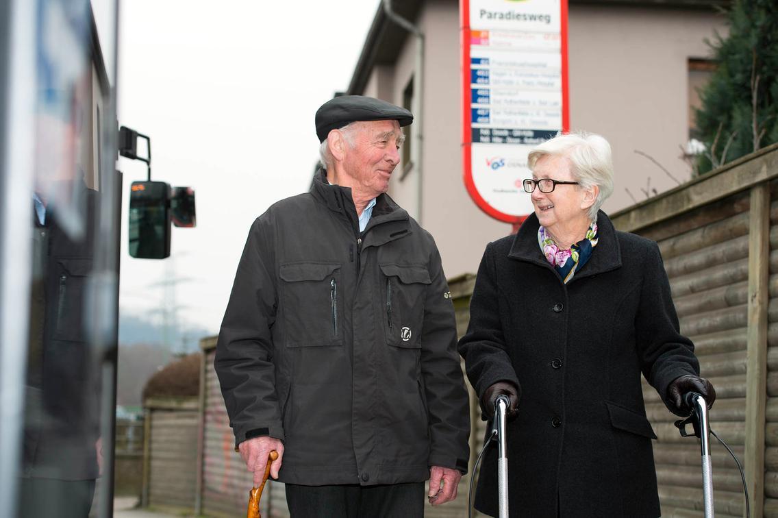 Älteres Paar steht an Bushaltestelle der VOS