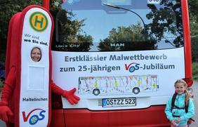 """VOS-Maskottchen Haltelinchen und die Jungkünstlerin Carla von der Grundschule Glandorf vor ihrem """"Bus-Kunstwerk"""""""