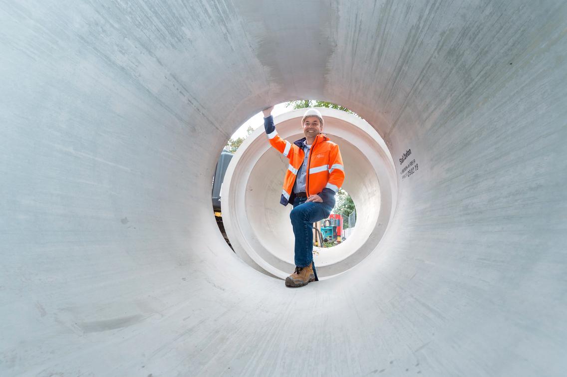 Mitarbeiter der SWO Netz GmbH schaut durch ein Kanalrohr