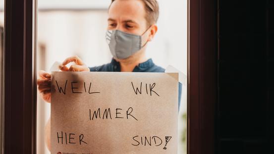 Mann mit Hinweiszettel am Fenster