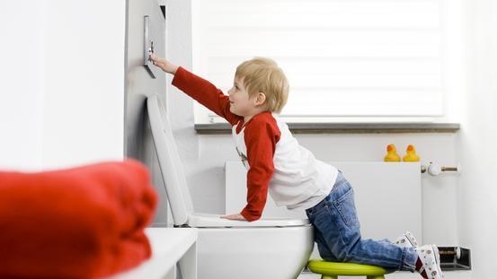 Kind drückt die Spülung der Toilette