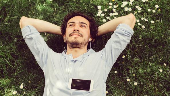 Mann entspannt auf wiese mit Kopfhörern