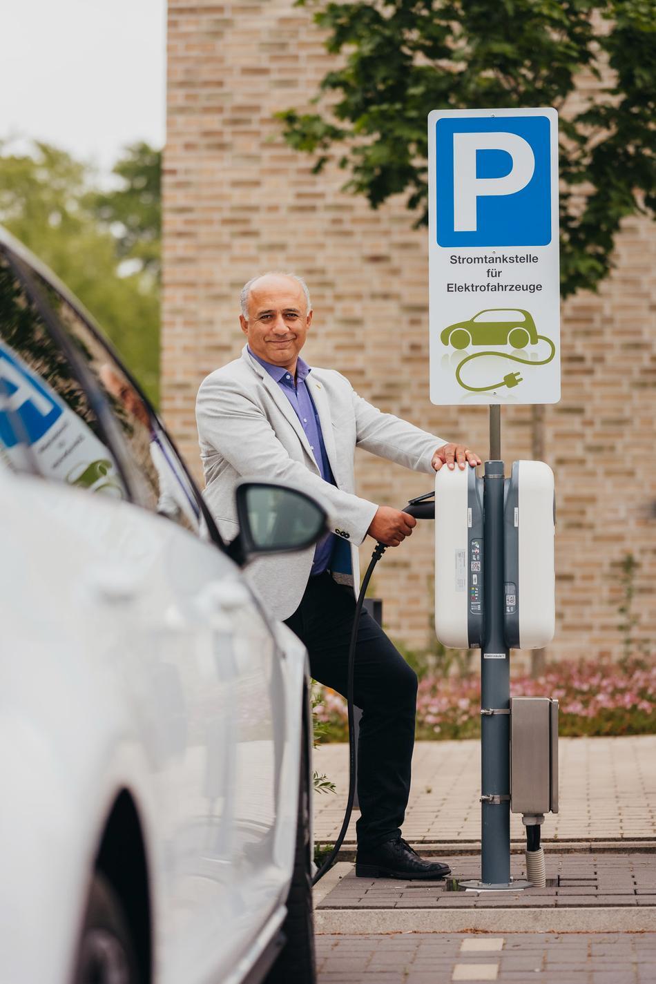 Geschäftsmann lädt E-Auto mit E-Ladebox