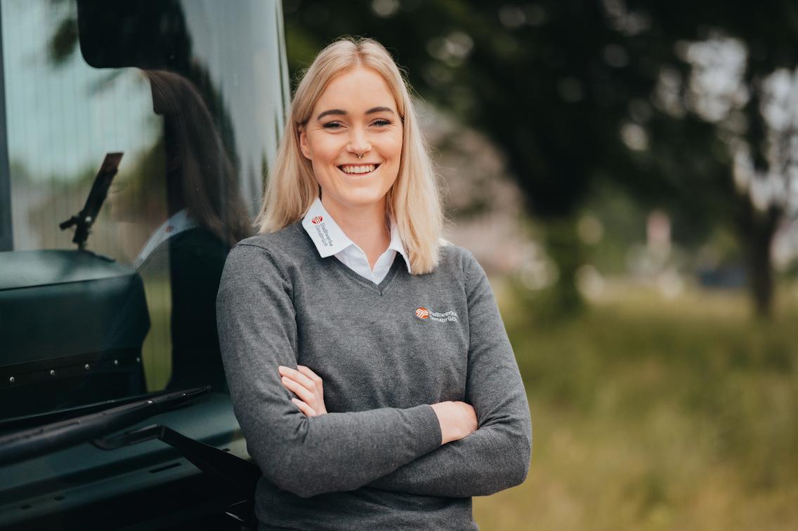 Frau steht lachend vor einem Bus