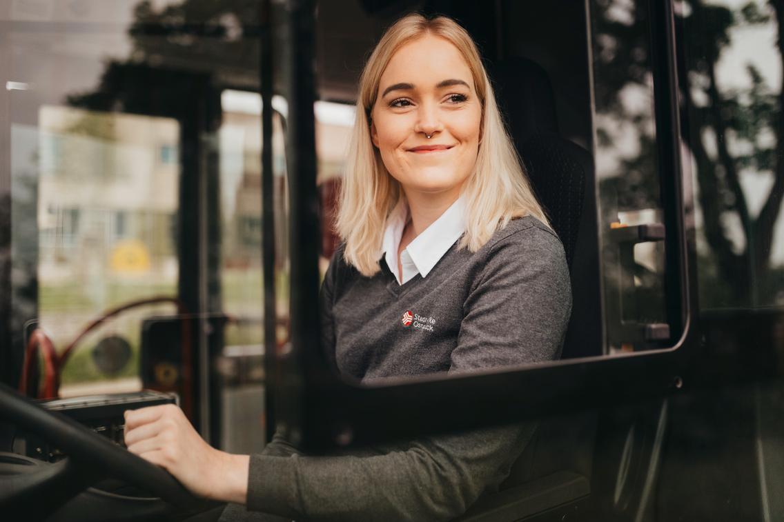 Busfahrerin schaut zufrieden aus dem Bus