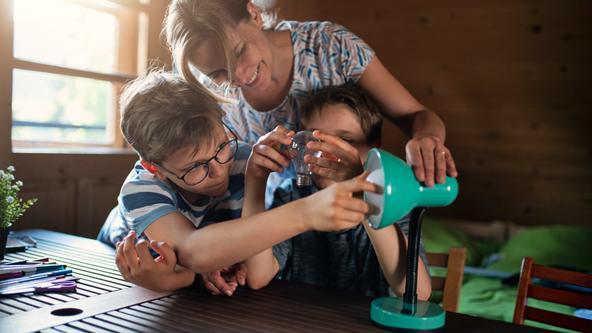 Familie wechselt Glühlampe um Energie zu sparen