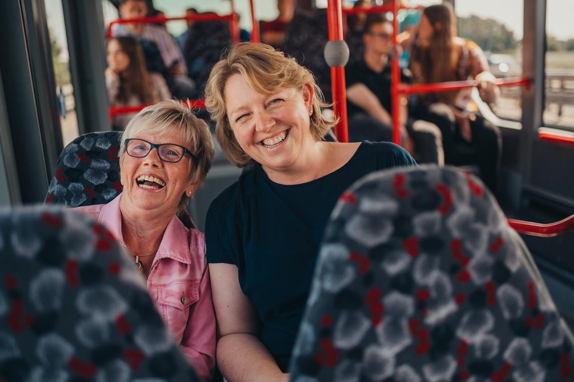 Zwei Lehrerinnen sitzen lächelnd im Bus der VOS