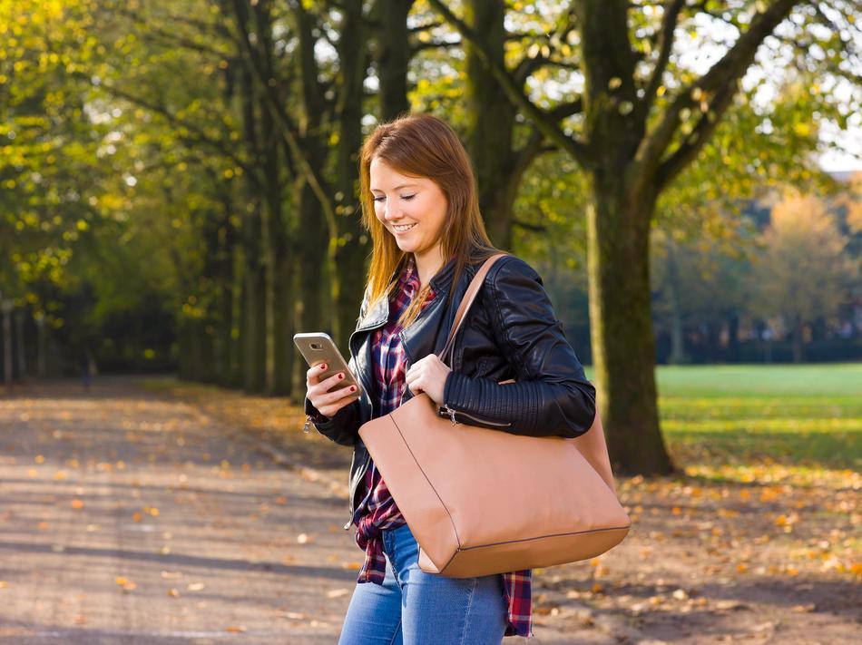 Frau mit Handy surft im Kundenportal Meine Stadtwerke