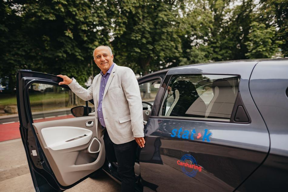 Mann öffnet die Tür des Carsharing Stadtteilautos