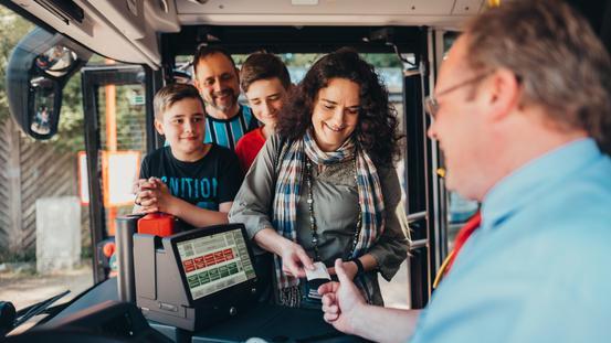 Kunden bezahlen Tickets im Bus der Verkehrsgemeinschaft Osnabrück (VOS)