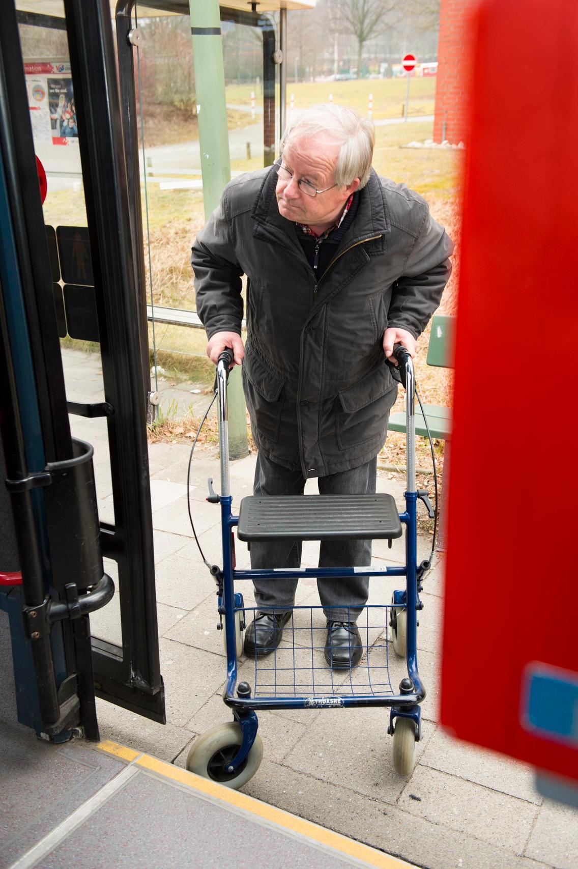 Mann mit Rollator steigt in den Bus ein