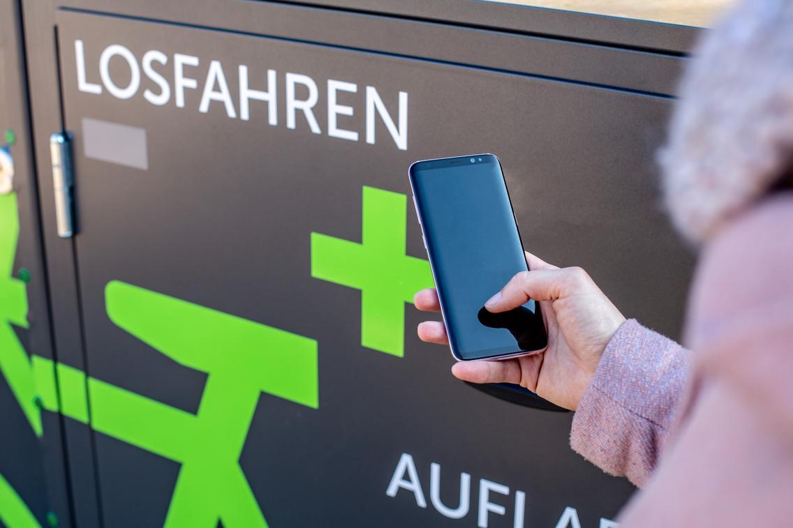 Frau meldet sich mit ihrem Handy bei Pedelec-Verleih an