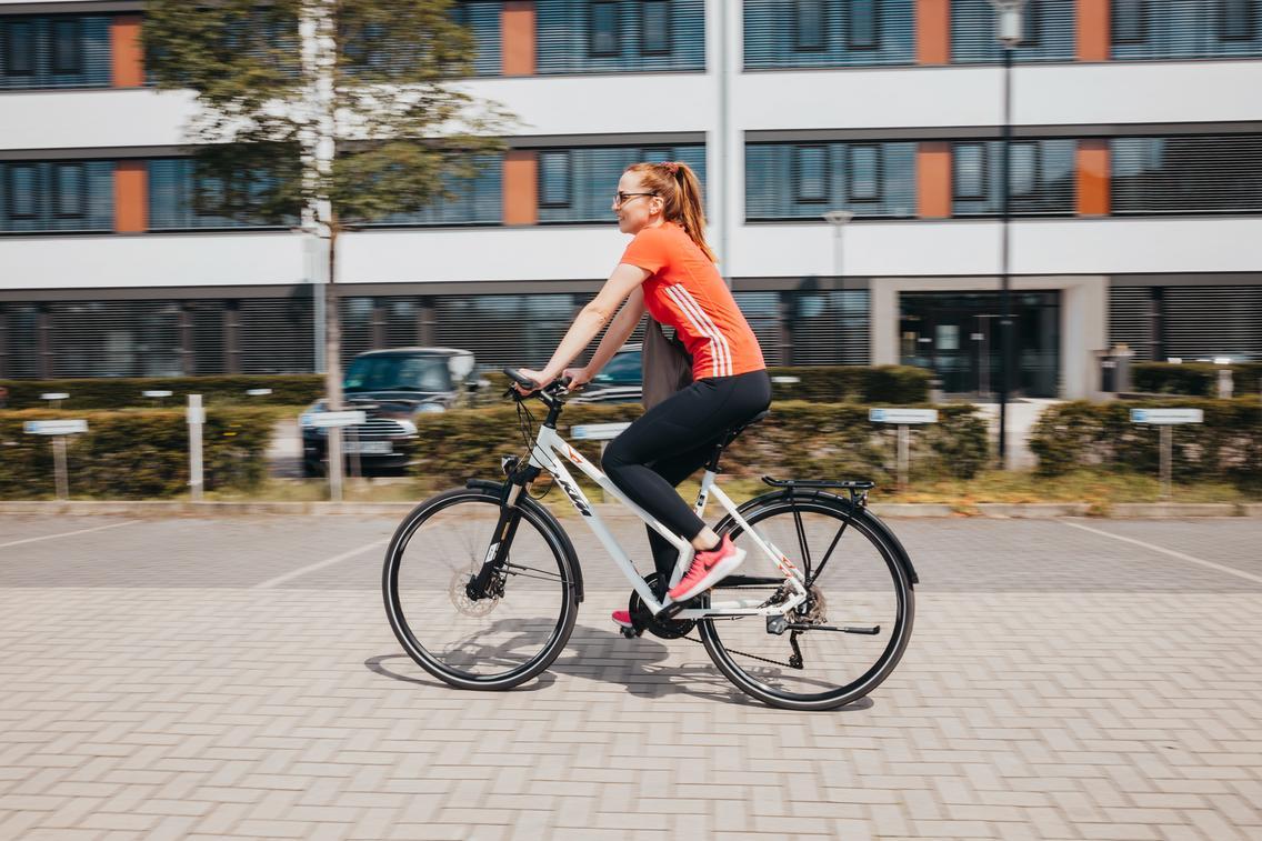 Frau fährt mit dem Fahrrad über das Betriebsgelände