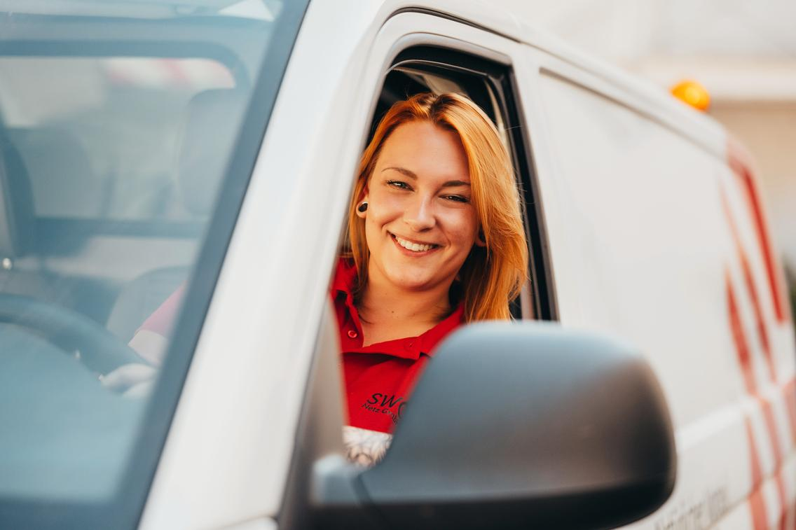 Frau sitzt lachend im Techniker-Auto
