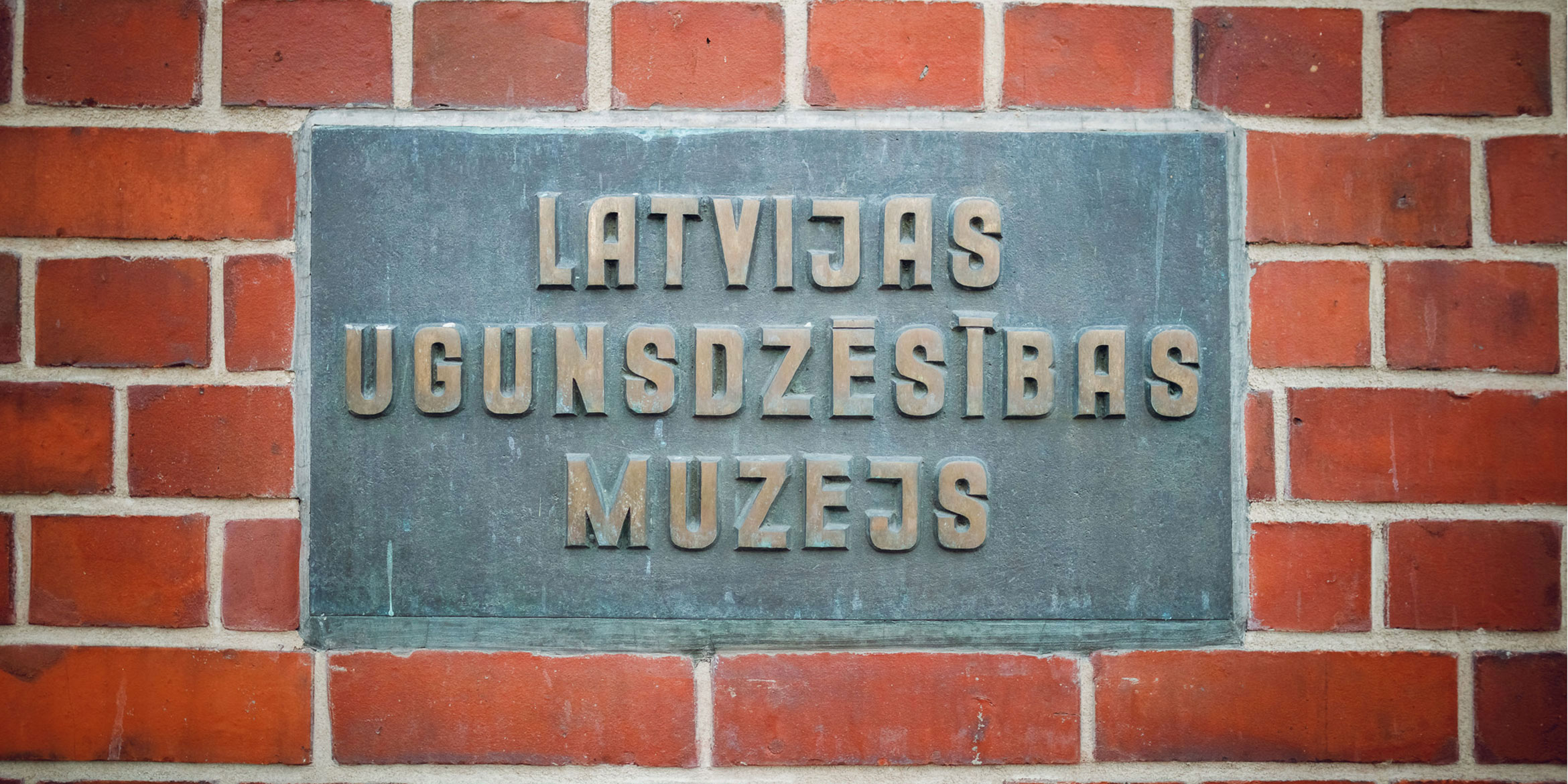 Plate on the wall of the fire museum in Riga