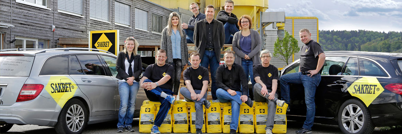 SAKRET Schweiz Mitarbeiter vor Dienstfahrzeugen