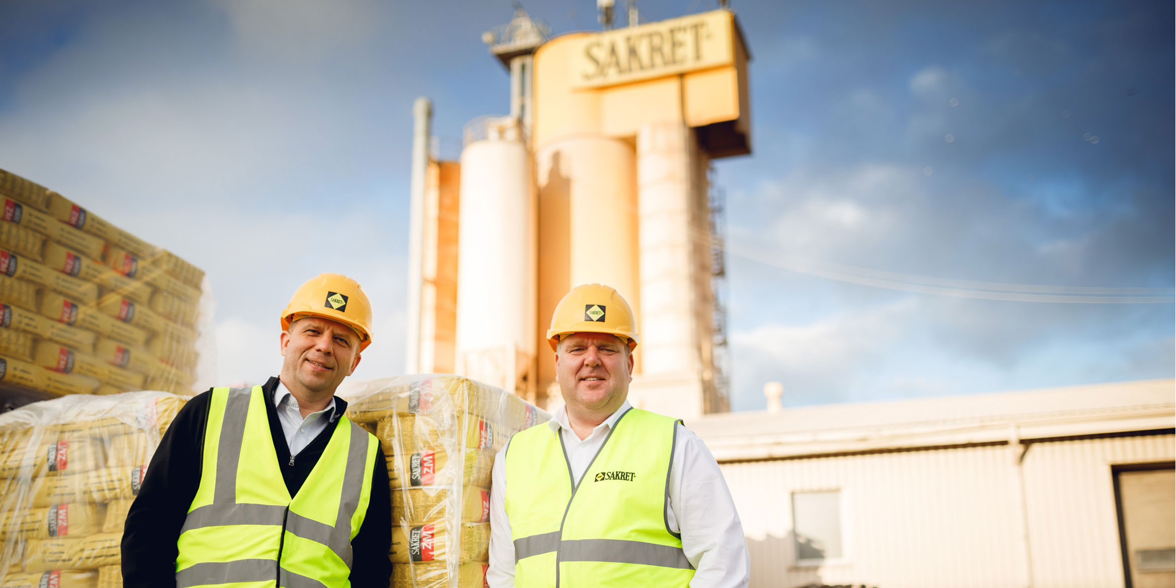 CEO's of SAKRET SIA in front of SAKRET bags and plant.