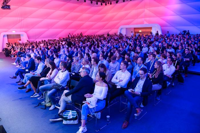 Publikum sitzt vor der Bühne und schaut den Referenten zu